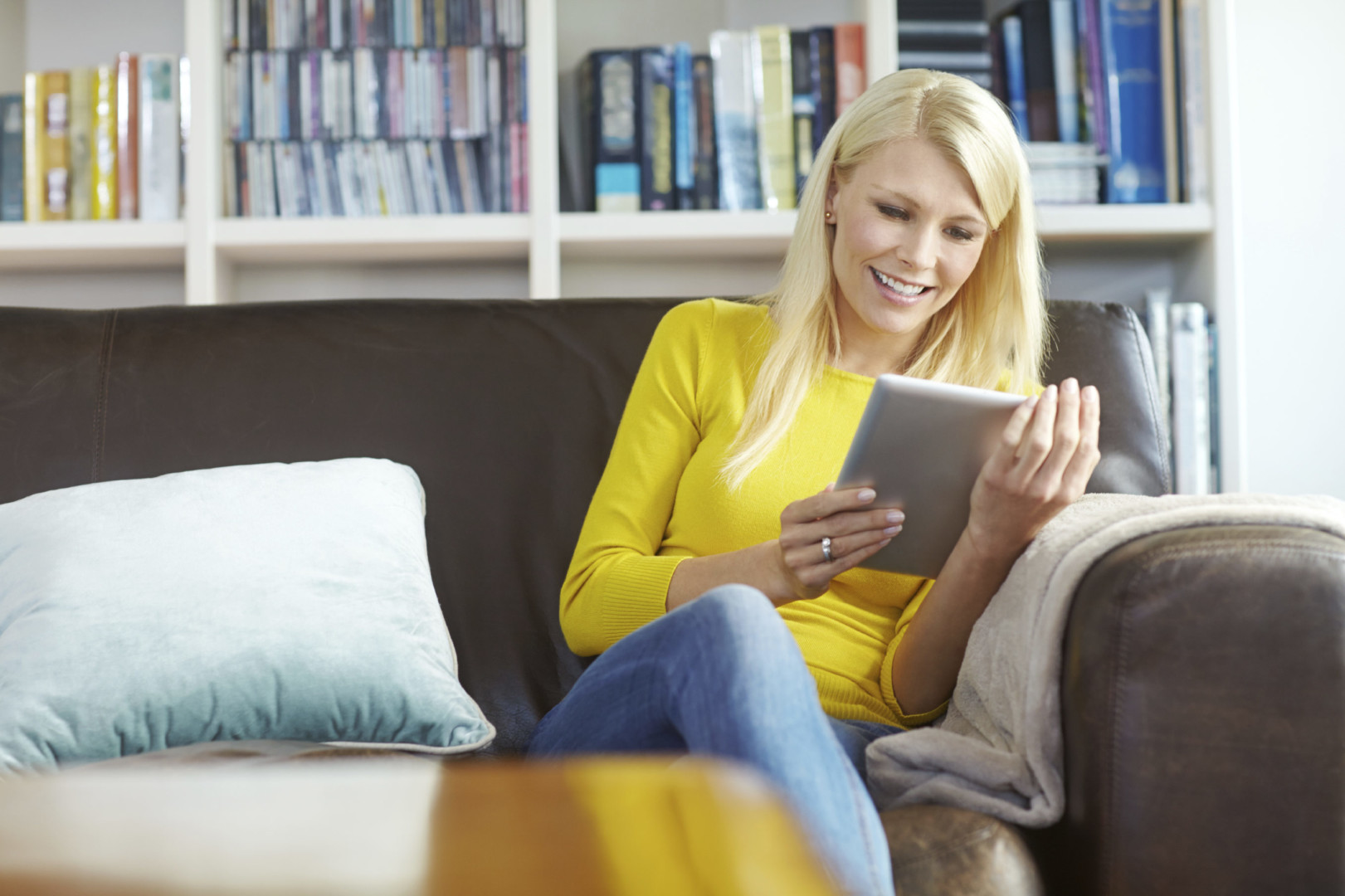 Shot of a beautiful young woman sitting on the sofa and using a digtal tablet